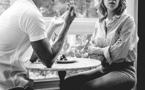 Matrimonio sentados en una mesa discutiendo