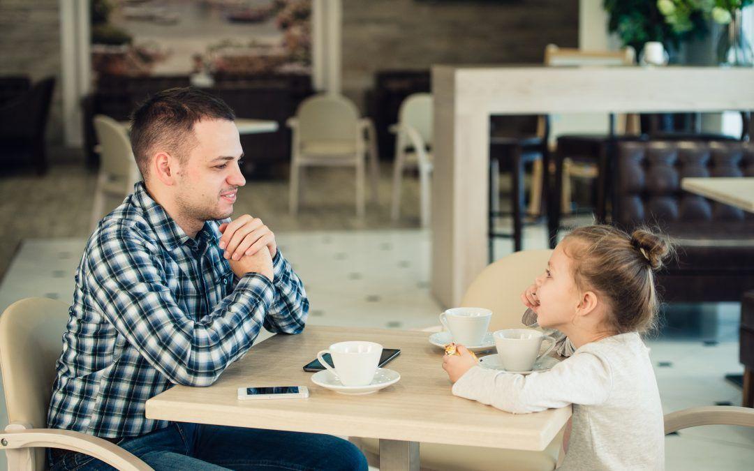 Padre con su hija sentados desayunado en una cafetería