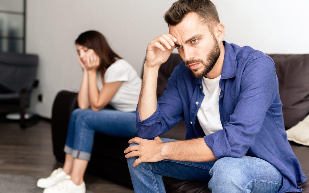 Matrimonio sentados en el sofa de casa separados y preocupados